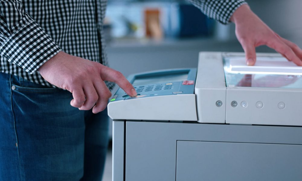 assistant makes copies of files in the copy machine